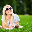 Female student in sunglasses with book on the grass — Stock Photo