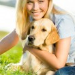 Woman embraces golden retriever on the grass — Stock Photo