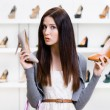 Woman can't choose pumps — Stock Photo #33813893