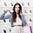 Girl keeps credit card in footwear shop — Stock Photo