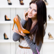 Half-length portrait of woman keeping stylish shoe — Stock Photo