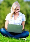 Fille avec ordinateur portable assis sur l'herbe — Photo