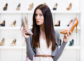 Woman can't choose pumps — Stock Photo