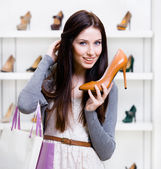 Half-length portrait of woman handing high heeled shoe — Stock Photo