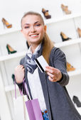 Girl showing credit card in footwear shop — Stock Photo
