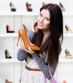 Half-length portrait of woman keeping stylish shoe — Stock Photo