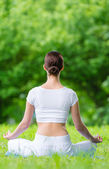 Backview of woman in asana position zen gesturing — Stockfoto