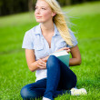 Girl holding book sits on the grass — Stock Photo