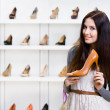Half-length portrait of woman keeping high heeled shoe — Stock Photo
