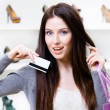 Young woman holds credit card in footwear shop — Stock Photo