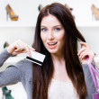 Young woman holds credit card in footwear shop — Stock Photo #34275275