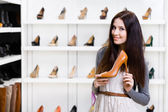 Half-length portrait of woman keeping high heeled shoe — Stockfoto
