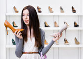 Woman can't choose high heeled shoes — Stock Photo