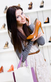 Half-length portrait of woman handing heeled shoe — Stock Photo