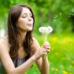 Постер, плакат: Woman blows dandelions in the park