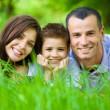 Happy family of three lying on grass — Stock Photo