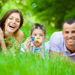 Family of three lying on grass and blows bubbles — Stock Photo #35648649