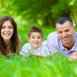 Happy family of three lying on grass with book — Stock Photo