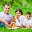 Happy family of three has picnic in park — Stock Photo
