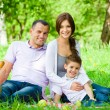 Happy family of three has picnic in green park — Stock Photo