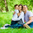 Family of three has picnic in park — Stock Photo