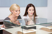 Two girls looking at showcase with jewelry — Stock Photo