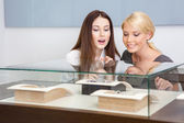 Two women looking at showcase with jewelry — Stock Photo
