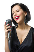 Female musician with closed eyes handing mic — Stock Photo