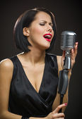 Female singer keeping microphone — Stock Photo