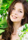 Beautiful woman near the blossomed tree — Stock Photo