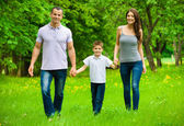 Full-length portrait of happy family of three — Stock Photo