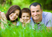 Happy family of three lying on grass — Stock Photo