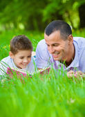 Father and son read book in park — Stock Photo