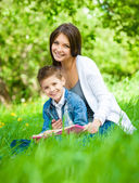 Mother and son with book in green park — Stok fotoğraf
