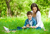 Mother and son with book in park — Stockfoto