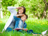 Mother and son with book cover eyes in park — Stock Photo
