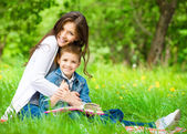 Mom and son with book in green park — Stock Photo