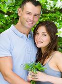 Paar omarmen in de buurt van bloemrijke boom — Stockfoto