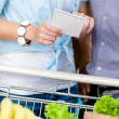 Close up of shopping list in hands of couple — Stock Photo #36532341