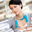 Pretty girl reads sitting at the desk — Stock Photo
