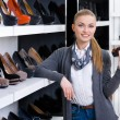 Stock Photo: Womwith shoe in hand chooses stylish pumps