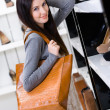 Woman choosing a pair of shoes in shop — Stock Photo #36533785