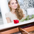 Portrait of female with red rose playing piano — Stock Photo