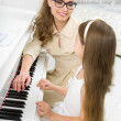 Stock Photo: Master teaches little girl to play piano