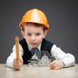 Little boy in hard hat with home model and ruler — Stock Photo #36535761