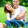 Man hugs girl sitting on grass in park — Stock Photo