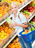 Girl at the shopping mall choosing vegetables — Stock Photo