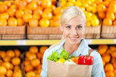 Girl hands paper bag with fresh vegetables — Stockfoto