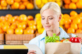 Girl hands bag with fresh vegetables — Stock Photo