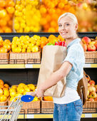 Girl with cart hands packet — Stockfoto